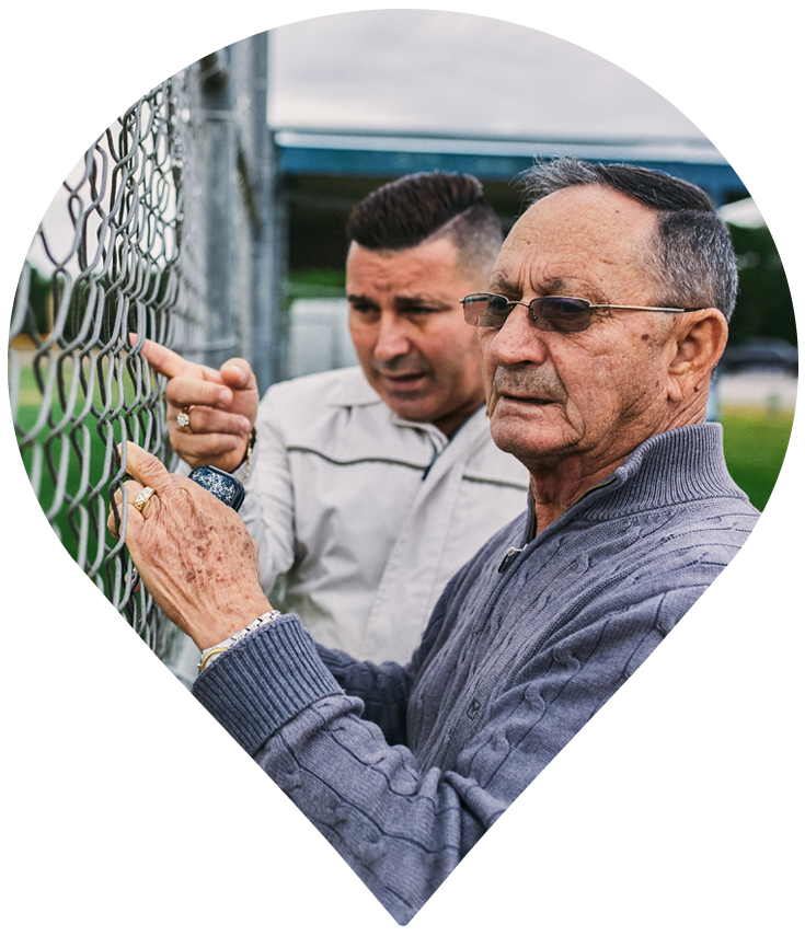 Pin of male participant and son looking and pointing through fence