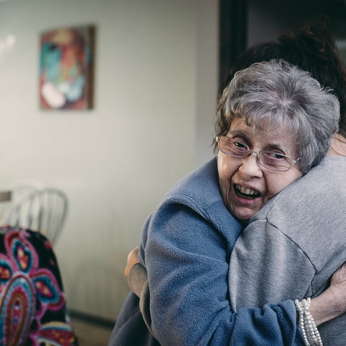 Care worker and elderly female participant hugging
