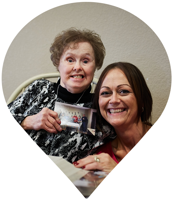 Pin of elderly female participant and care worker showing photo and smiling at camera