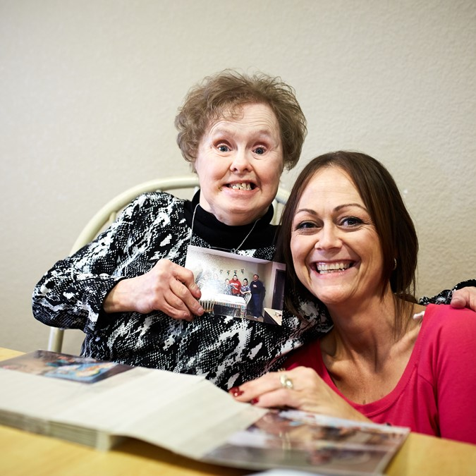 Elderly woman with mental disability sitting at kitchen table with a coloring book and her care worker