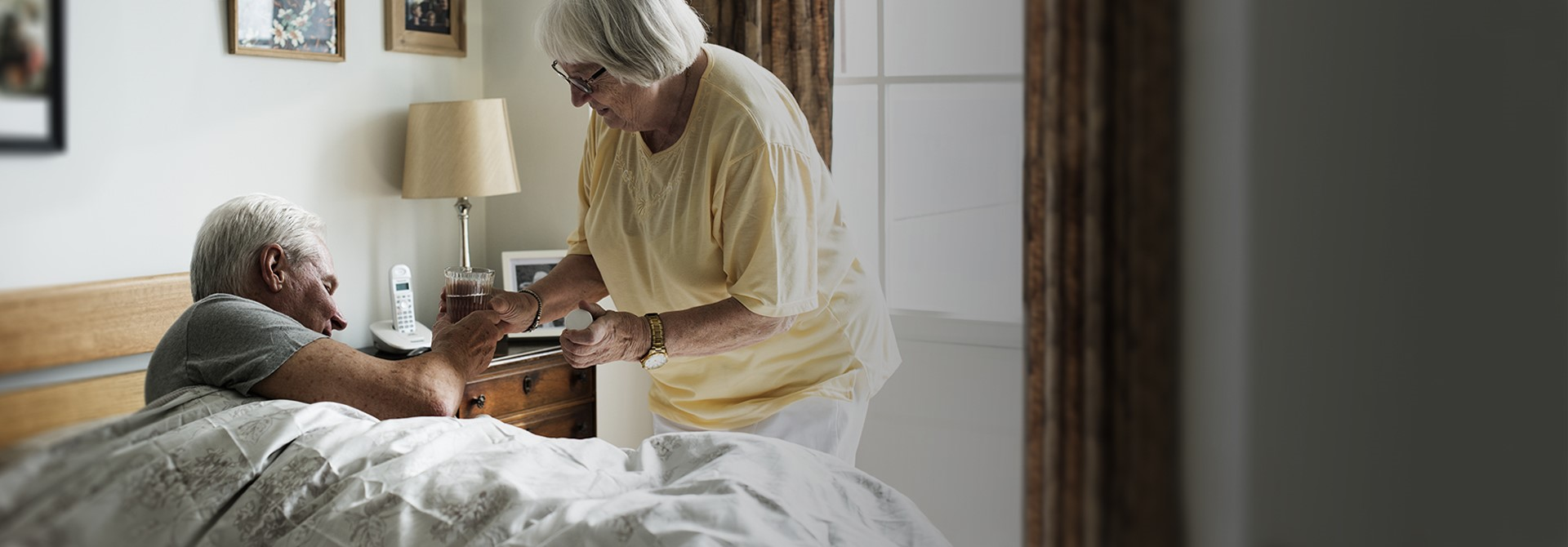 Elderly woman handing a glass of water to elderly man laying in bed